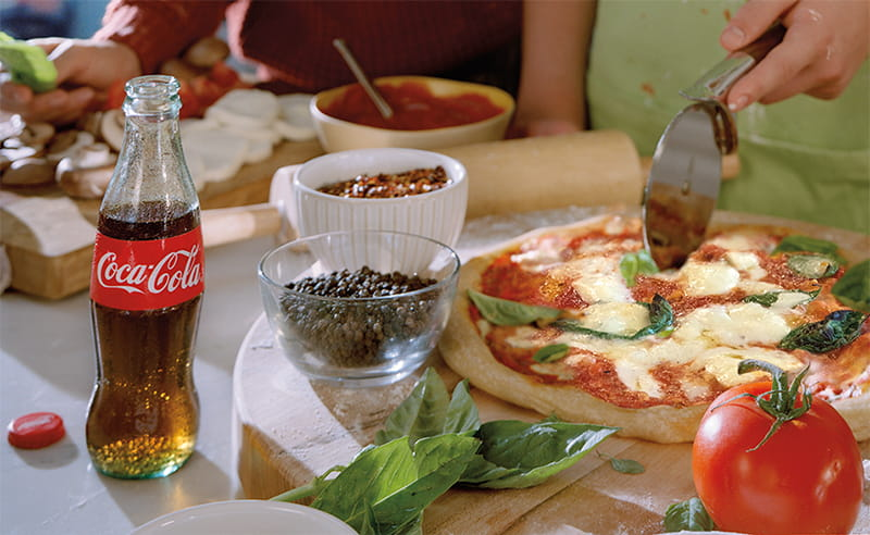 A person slicing a pizza next to a Coca-Cola bottle.